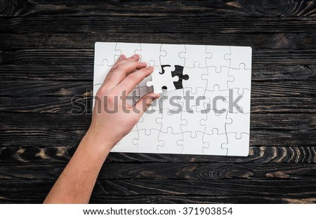 hand completing wthite puzzle with the last piece - stock photo