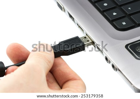 Hand connecting USB cable to laptop computer isolated on white background - stock photo