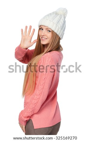 Hand counting - five fingers. Portrait of woman on white background wearing woolen hat and sweater showing five fingers, giving high five gesture - success and winning concept. - stock photo