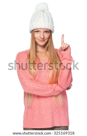 Hand counting - one finger. Portrait of woman on white background wearing woolen hat and sweater showing one finger, directing up, idea concept - stock photo