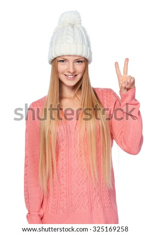 Hand counting - two fingers. Portrait of woman on white background wearing woolen hat and sweater showing two fingers, V sign - stock photo