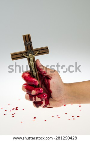 Hand covered with blood is holding a cross, white and grey gradient background. - stock photo