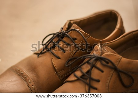 Hand crafted Brown Leather Shoes kept on a Wooden Floor on a Sunny Day with a nice Bokeh Background