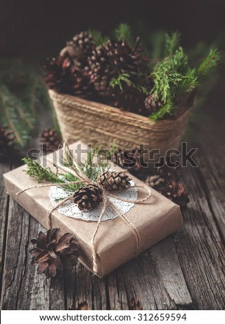 Hand crafted gift on rustic wooden background with with fir branches and cones  - stock photo
