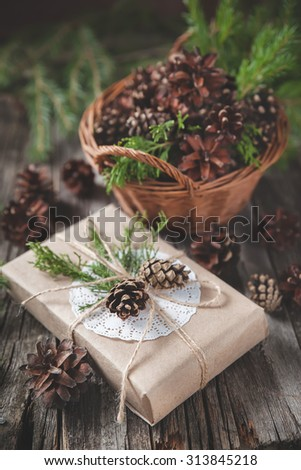 Hand crafted gift on rustic wooden background with with fir branches and cones, toned image - stock photo