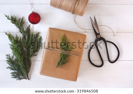 Hand crafted gift on white wooden background with Christmas decoration. - stock photo