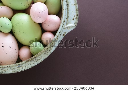 Hand crafted pastel pink and green easter eggs in speckled pottery bowl on aubergine background with room for your text - stock photo
