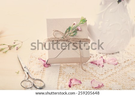 Hand crafted present box with flower petals - stock photo