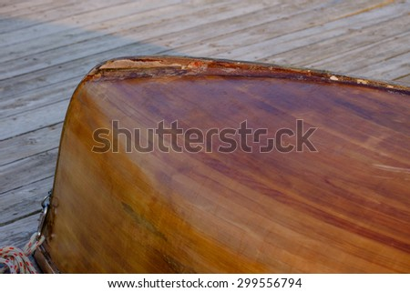 Hand crafted wooden rowboat laying on a deck upside down at dusk displaying it's keel - stock photo