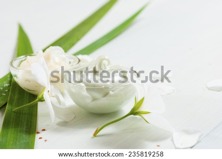 hand cream and face cream with white flowers on bright wooden table