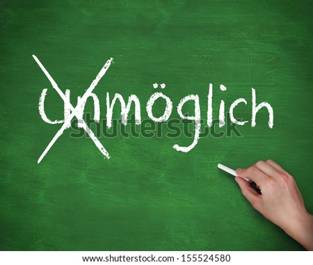 Hand crossing out the german word for impossible on a green board - stock photo