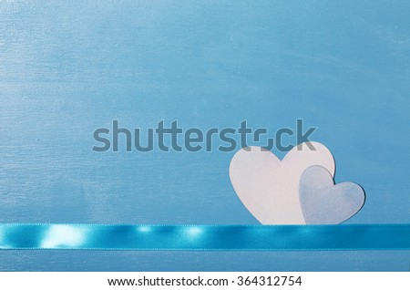 Hand cut hearts and ribbon on blue wood texture background - stock photo