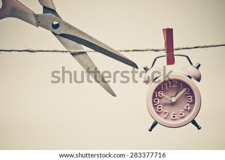 hand cutting a rope with a clock hung on by a wooden clip - importance of time
