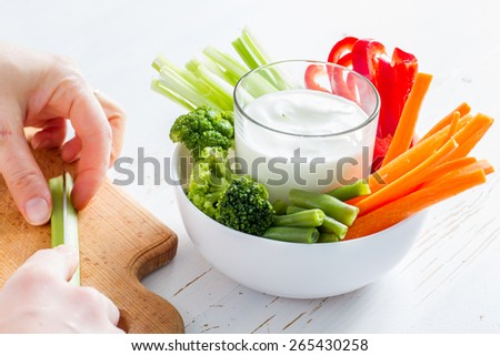 Hand cutting celery on wood board, white bowl with carrot, celery, pepper, broccoli and green beans, yogurt sauce, white wood background - stock photo