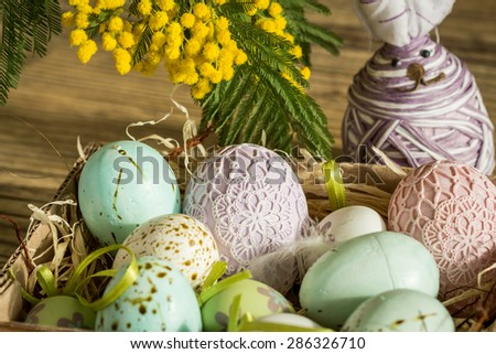 Hand decorated Easter Eggs and speckled birds eggs in straw with a branch of colorful yellow clusters of mimosa flowers in a natural country Easter background