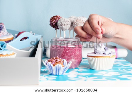 hand decorating cakepops and cupcakes - stock photo