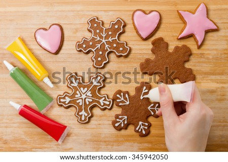 Hand decorating Christmas gingerbread snowflakes biscuits. Decorating process with sweet icing