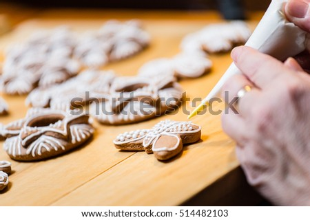 Hand decorating the traditional Christmas gingerbread cookies