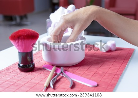 hand dipped in a white bowl ready to a manicure treatment on a placemat on a table, near a nail file, a brush and a cuticle remover at a beauty salon - stock photo
