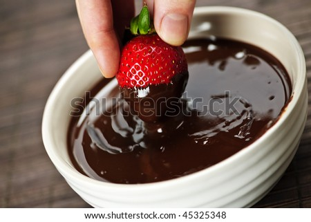 Hand dipping fresh strawberry in melted chocolate - stock photo