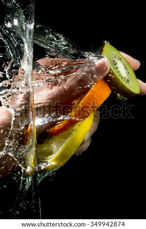 Hand dipping fruit under water. Wash fruit. - stock photo
