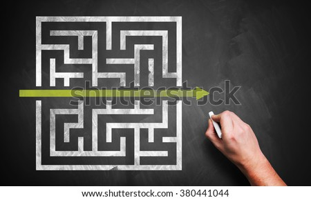 hand drawing a shortcut to a maze on a chalkboard - stock photo