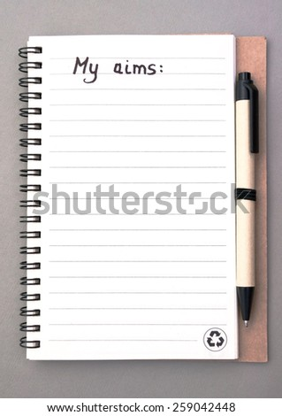 Hand drawing aims list on notebook from recycling paper on grey background with handle - stock photo