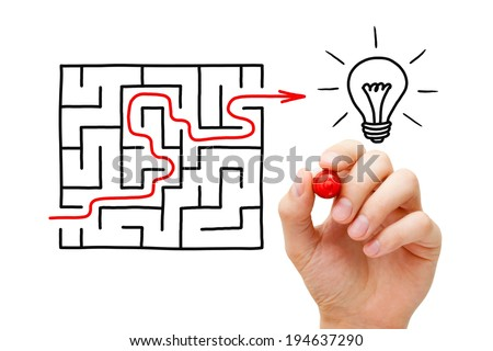 Hand drawing an red arrow going through a maze to a glowing light bulb. It's hard to find a great idea. - stock photo
