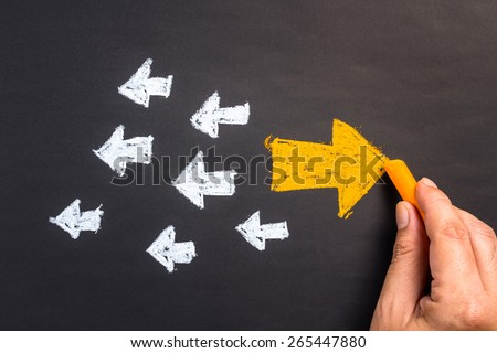 Hand drawing arrow sign in opposite direction from others - stock photo