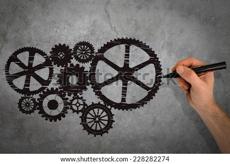 Hand drawing black gears on gray wall - stock photo