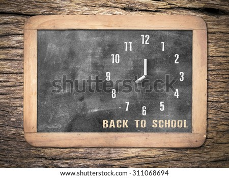 "Hand-drawing clock with text for ""Back to school"" on grungy chalk blackboard. - stock photo"