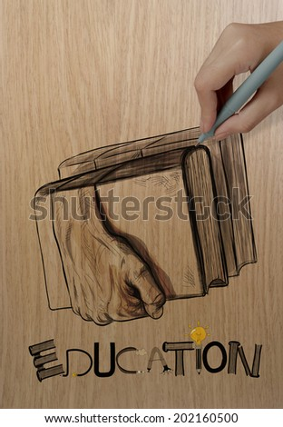 hand drawing hands holding the books on wood background as creative concept  - stock photo