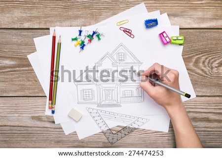 Hand drawing house on a wooden background