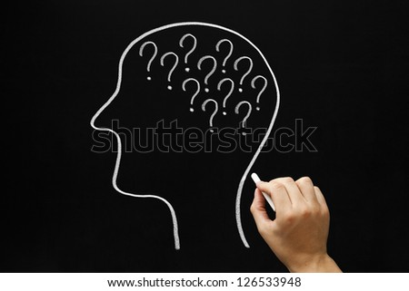 Hand drawing Human head and many question marks with white chalk on blackboard. - stock photo