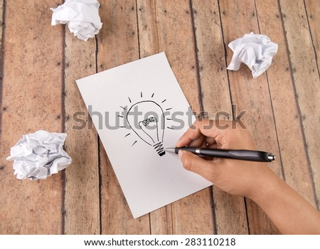Hand drawing light bulb on a note pad. Concept for idea, creativity, imagination and perserverance - stock photo