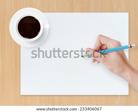 Hand drawing pencil on white paper sheet with coffee cup on wood background.