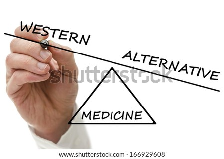 Hand drawing scale with Western versus alternative medicine. - stock photo