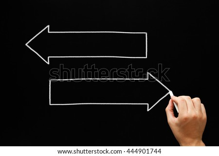 Hand drawing two blank arrows with white chalk on blackboard. Concept with copy space for text. - stock photo