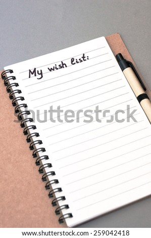 Hand drawing wish list on notebook from recycling paper on grey background with handle - stock photo