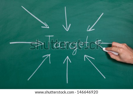 Hand Drawn Arrows Gathering Over Target On Chalkboard - stock photo