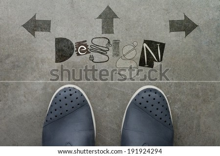 Hand drawn DESIGN design word on front of business man feet as concept  - stock photo