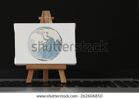 hand drawn globe with social network diagram on canvas and wooden easel on laptop computer as concept Elements of this image furnished by NASA - stock photo