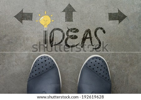 Hand drawn IDEA design word on front of business man feet as concept  - stock photo