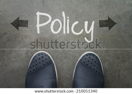 Hand drawn policy word on front of business man feet as concept - stock photo