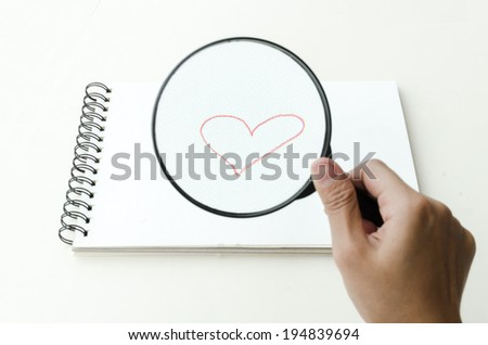 Hand-drawn red romantic heart drawn on a blank page in a sketch book and viewed through a magnifying glass held in the hand of a man, conceptual of love and romance - stock photo
