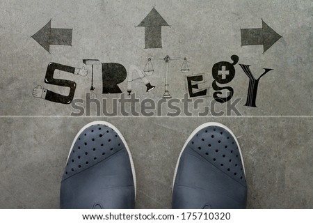 Hand drawn STRATEGY design word on front of business man feet as concept - stock photo