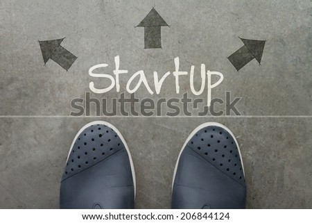 Hand drawn STRATUP design word on front of business man feet as concept  - stock photo