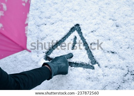 Hand Drawn Warning Sign - A woman with umbrella sketches a warning sign drawing in the snow on a car hood.  - stock photo