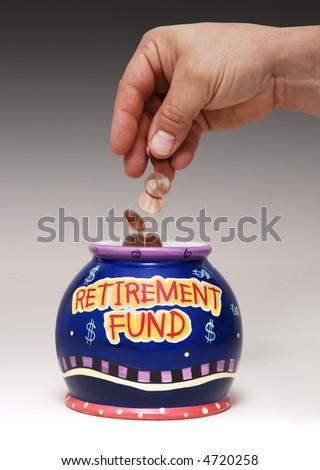 """hand dropping pennies into a jar labeled """"Retirement Fund"""" - stock photo"""