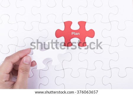 Hand embed missing a piece of puzzle into place, red space with word PLAN concept